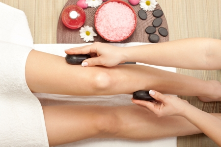 massaging of the human legs with hot mineral stone photo