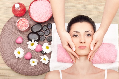 young cute woman receiving a facial massage at spa center photo