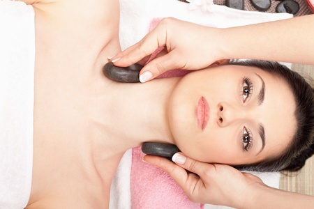 young woman receiving spa treatment of neck with dark stone, top view photo