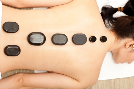 massage females back with hot mineral stone  photo