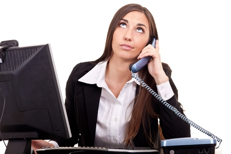 business woman talking with boring client on phone and working on  computer photo