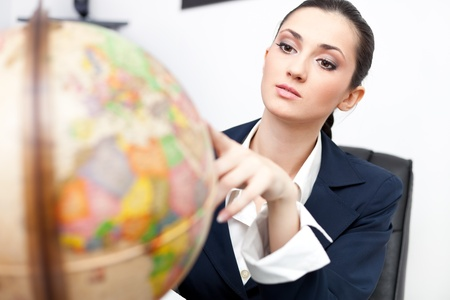 young businesswoman in office looking globe Stock Photo - 9617083