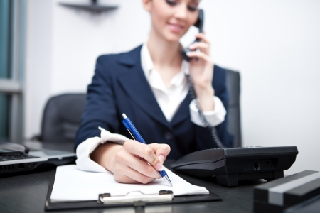 appointment: businesswoman using phone, taking notes at office desk