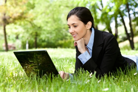 young pretty girl working on laptop outdoor, lying on grass,  caucasian 20 years old photo