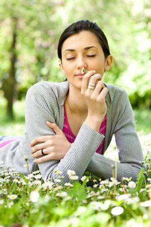 niña tendido en la pradera y disfrutando en olor de flores Foto de archivo