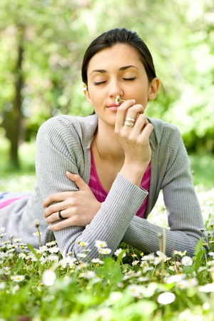 young girl laying in meadow and enjoying in smelling flowers photo