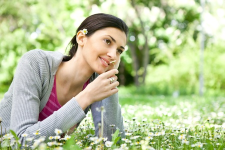 smiling young girl in spring park smelling flower photo