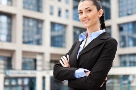 financial leadership: joven y atractiva empresaria en traje, imagen es tomada al aire libre en una calle