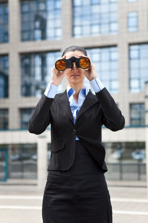 smiling young business woman looking through the binoculars in front an office building photo