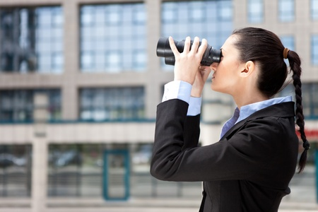 concurrence: businesswoman with binocular in front  office building