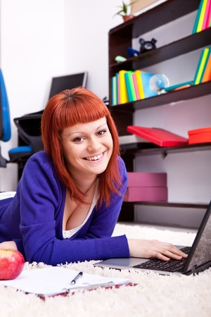 teen girl studying at home in room with books and laptop, girl smiling and looking at camera photo