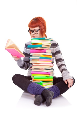 female student sitting with pile of books and reading book photo