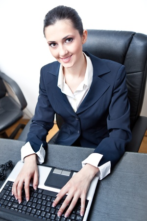 happy caucasian businesswoman typing in office Stock Photo - 9653427