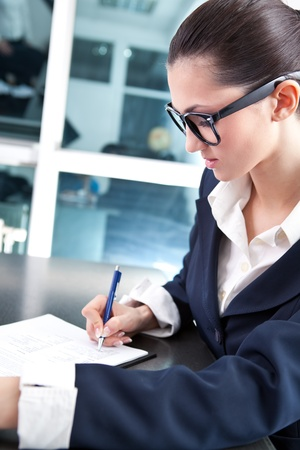 busy secretary or businesswoman writing in office Stock Photo - 9653414