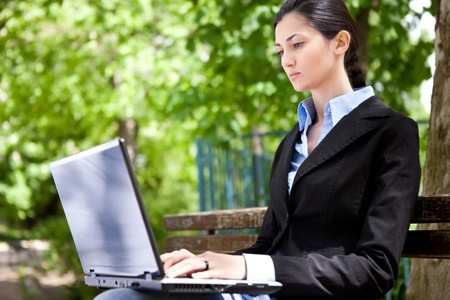 businesswoman sitting on bench in park and working photo