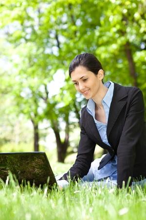 laptop outside: young businesswoman working on laptop in park Stock Photo