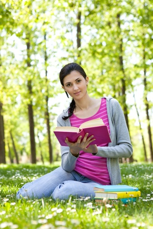 cute girl reading a book on the grass outside photo