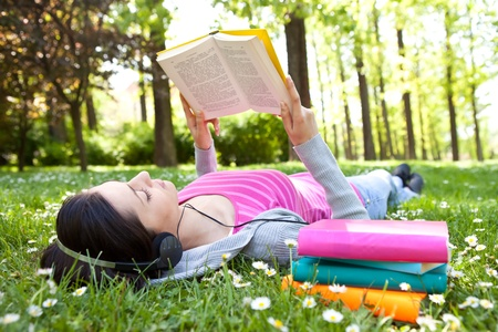 music book: girl lying on grass and relaxing  with book and music Stock Photo