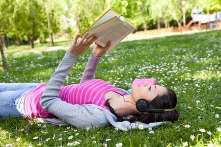 젊은 여자 헤드폰을 사용하고 책을 읽고 잔디에 음악을 듣고