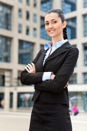 businesswoman standing outdoors by building smiling photo