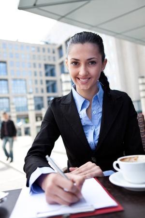 businesswoman working on coffee break in restaurant outdoor photo