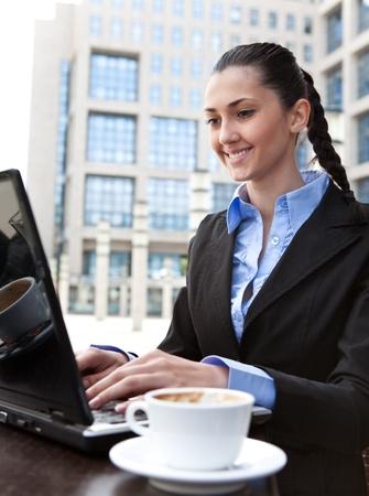 businesswoman working on coffee break, outdoor photo