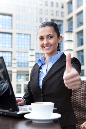 smiling business woman working on laptop and shoving thumbs up photo