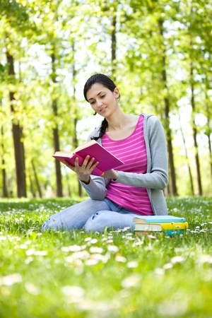 young beautiful girl reading a book outdoor photo