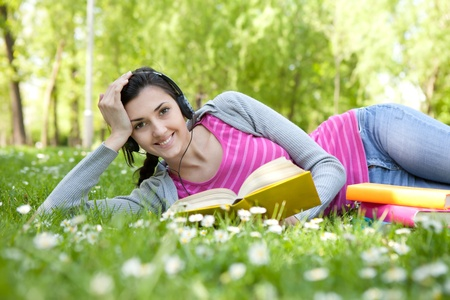 smiling woman with book in nature listening music through headset photo