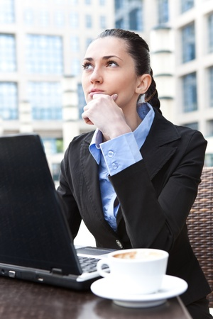 young business woman thinking, sitting in cafeteria, outdoor photo