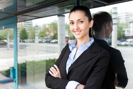 young businesswoman stands with her arms crossed outside an office building. she is smiling and looking at the camera,  horizontal shot  photo