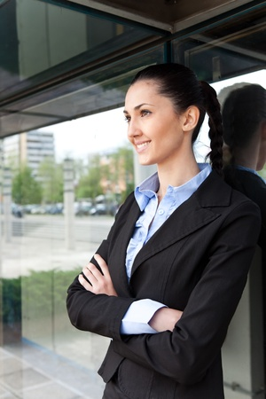 businesswoman standing outdoors by her building office,  smiling with her arms crossed  photo