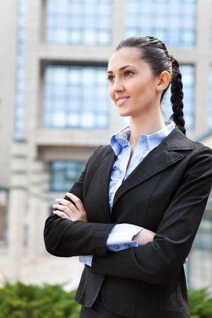 attractive businesswoman smiling while standing in front of an office building, vertical shot  photo