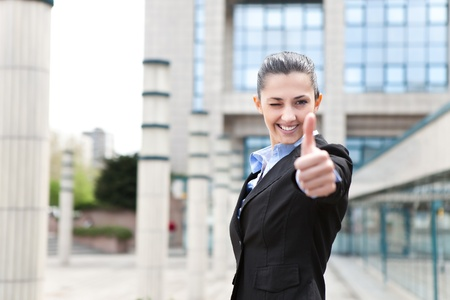 successful businesswoman winking and giving thumbs up, standing  outdoor front business office photo