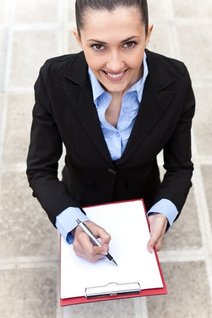businesswoman standing outdoor and making note, smiling woman looking at camera, top view  photo