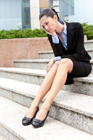 jobless: jobless businesswoman,  depressed and worried woman sitting on stairs office building