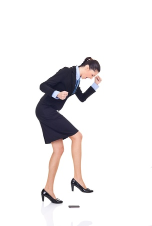 businesswoman angry on her cellphone, smashing phone with leg, isolated on white background concept,