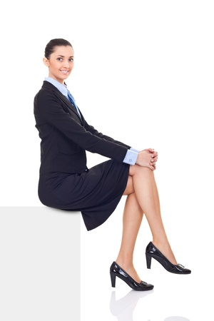 sitting: businesswoman sitting on horizontal banner edge,  smiling woman showing sign with lot of copy space, isolated on white background in full body