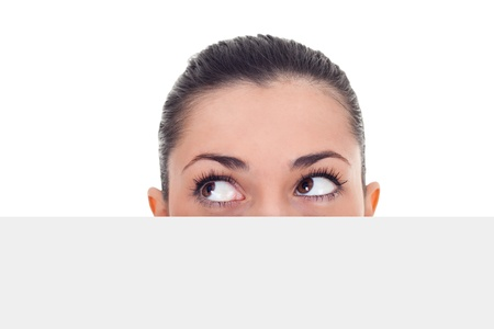 woman peeking hidden over blank billboard and looking in side,  isolated on white background  photo