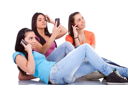 three girls having fun with cell phones, isolated white background Stock Photo - 9769192