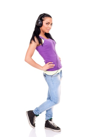 young girl with big black headphone  listen music, standing on white background photo