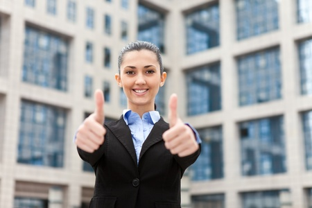 successful businesswoman outdoor showing thumbs up photo