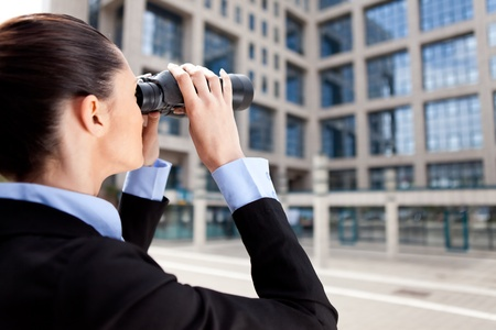 concurrence: businesswoman looking through binoculars in competition building