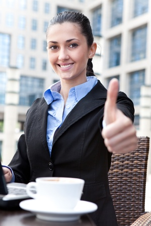 successful businesswoman on coffee break shoving thumbs up photo