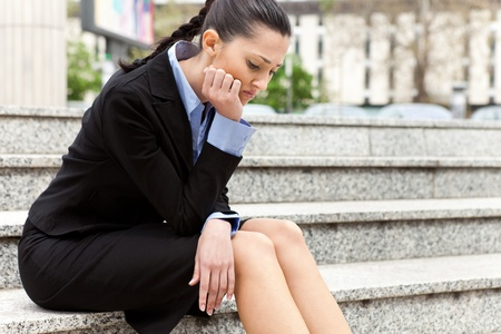 fired: businesswoman sitting on the stairs of the company troubled after getting the news he was fired
