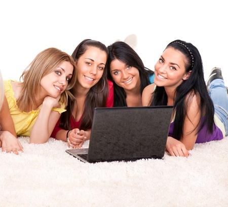 adolescentes chicas:  las ni�as adolescente recae en port�tiles sobre un fondo blanco, cuatro hermosa, estudiantes alegres, aislados en blanco
