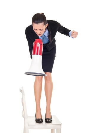 angry businesswoman shouting through megaphone on employers, standing on chair, isolated on white background photo