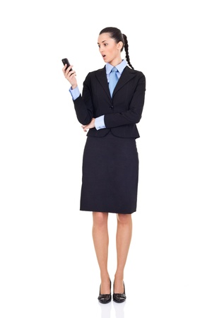 surprised business women looking in cellphone, isolated on white background photo