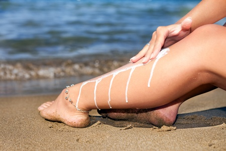Woman on the beach applying sun protection lotion on leg for skincare photo