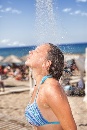 Mujer bajo la ducha en la playa